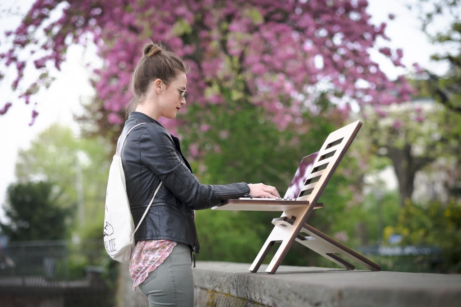 a girl typing on her laptop outdoors